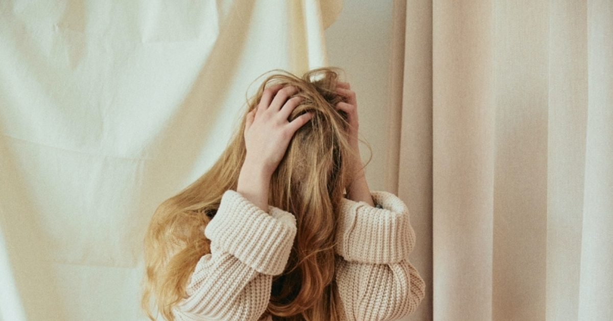 Image for Living with Depression: Woman running her hands through her hair and seeming distressed.