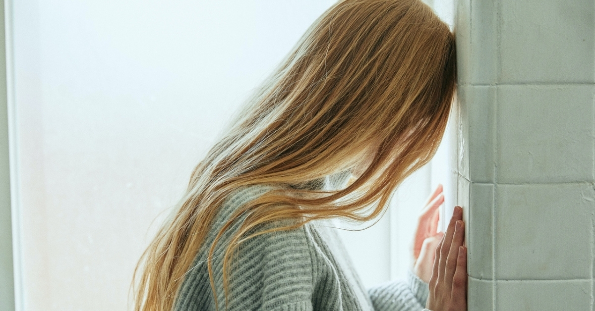 """Image for """"Living with Depression"""": Woman pressing her head against a wall."""