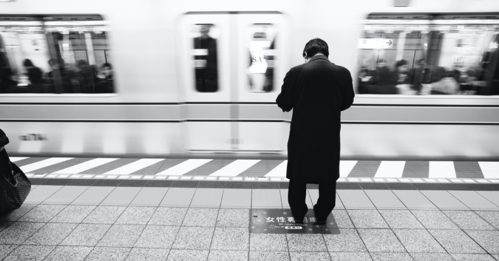 """TEXT for """"Handling homesickness"""": Image of a person standing alone on a train platform."""